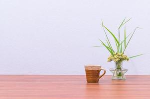 caneca de café e vaso de flores na mesa foto