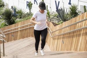 mulher correndo com uma camiseta branca, malhando em uma escada de madeira