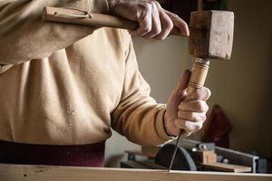 carpinteiro trabalhando com um martelo de madeira e uma goiva foto