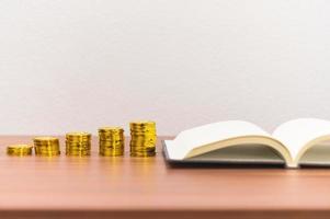 livro e pilhas de moedas na mesa foto