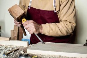 mãos de carpinteiro com cinzel na bancada de madeira foto