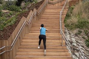 mulher correndo com uma camisa azul e subindo uma escada de madeira