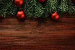Natal e ano novo com decoração de bolas vermelhas na vista superior do fundo da mesa de madeira com espaço de cópia