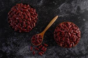 feijão vermelho em tigelas de madeira na superfície preta da cozinha foto
