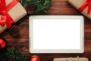 Modelo de maquete de computador tablet feliz Natal com decorações de folhas de pinho