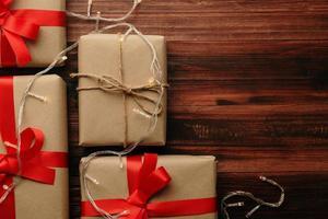 Natal e ano novo com caixas de presente e decoração de luz de corda na vista superior do fundo da mesa de madeira com espaço de cópia