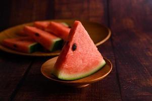 melancia cortada em pedaços sobre uma mesa de madeira foto