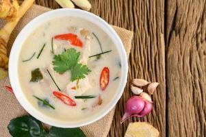 tom kha kai, sopa de coco tailandesa na mesa de madeira da cozinha