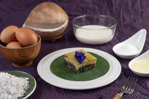 arroz preto pegajoso em uma folha de bananeira em um prato branco com flores de ervilha-borboleta foto