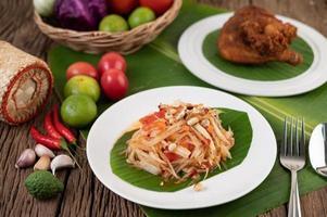 salada tailandesa de mamão com folhas de bananeira e ingredientes frescos foto