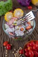 salada de frutas e vegetais em uma tigela de vidro na mesa de madeira foto