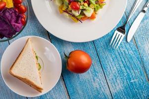 Salada fresca em um prato branco com um sanduíche e tomates foto