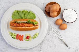 linguiça no pão e alface coberta com molho e ovos com farinha