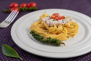 espaguete gourmet lindamente arranjado em um prato branco foto