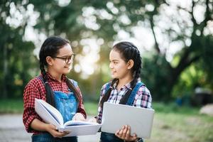duas meninas estudando e conversando em um parque