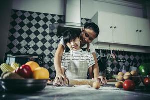 menina e mãe fofas de aventais achatando massa na cozinha de casa