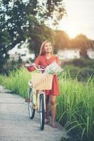 jovem mulher asiática andando de bicicleta em um parque foto