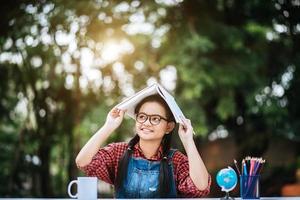 jovem com um livro na cabeça no parque