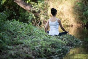 mulher em pose de ioga ao ar livre na natureza