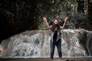 jovem se divertindo sob uma cachoeira na floresta