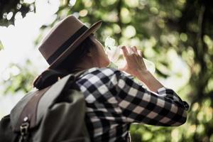 jovem bebendo água enquanto viaja na floresta