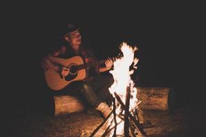 jovem sentado ao redor da fogueira tocando violão foto