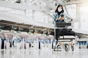 mulher usando máscara com carrinho de bagagem