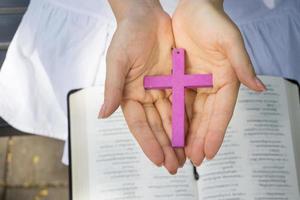 mãos de mulher segurando cruz de madeira foto