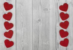linha de corações vermelhos nas laterais de um fundo de madeira branco e cinza. conceito de dia dos namorados