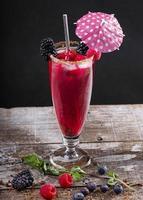 Coquetel de frutas da floresta em um copo sobre uma base de madeira decorada com amoras
