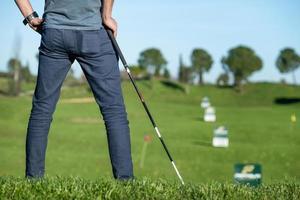 jogador de golfe com boné apoiado em um clube de golfe olhando para o campo