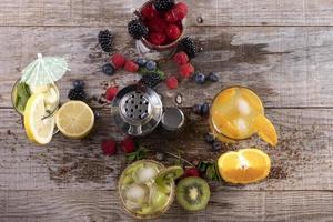 diferentes tipos de sucos de frutas acompanhados de um shaker de metal sobre uma base de madeira. conceito de vida saudável foto