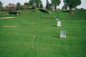 vista panorâmica de um campo de prática de golfe com sinais de metros atingidos.