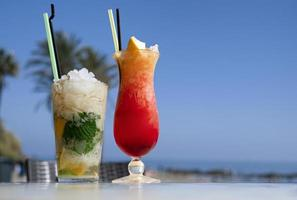 coquetel de mojito e san francisco em uma mesa de bar na praia. foto