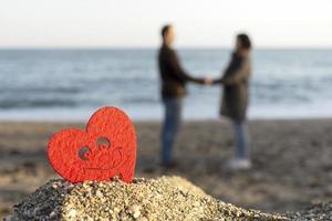 coração vermelho em uma montanha de areia à beira-mar com um casal de amantes no fundo. conceito de são namorados foto
