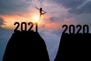 silhueta de mulher saltando sobre o número 2020 a 2021 foto