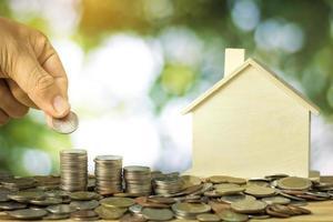pilhas de moedas e casa de madeira