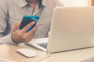 trabalhando em casa com um laptop e telefone foto