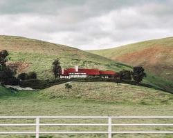 utah, 2020 - casa vermelha e branca em campo de grama verde perto de uma montanha sob nuvens brancas durante o dia