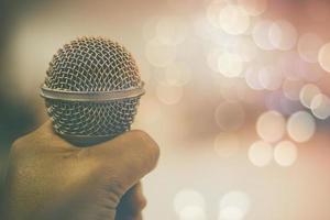 mão segurando o microfone foto