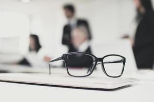 um par de óculos em uma sala de reuniões