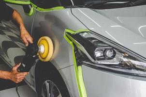 mecânico polindo um carro foto