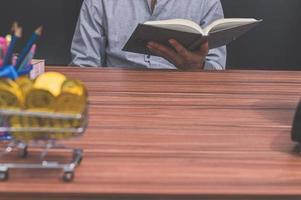 homem lendo um livro em sua mesa