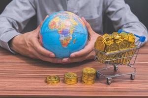 mão segurando um globo e moedas na mesa