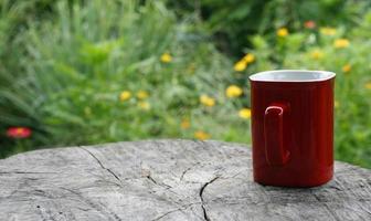 caneca vermelha de café na mesa de madeira contra verde desfocado