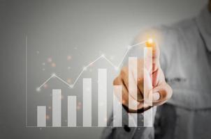 mão apontando para o crescimento em um gráfico de barras foto