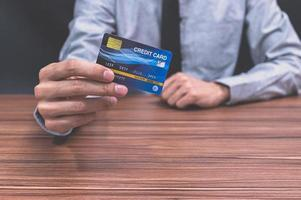 homem segurando um cartão de crédito