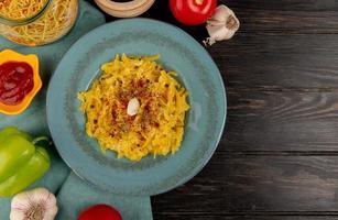 vista superior de macarrão macarrão em prato com tomate pimenta ketchup alho em pano azul e fundo de madeira com espaço de cópia foto