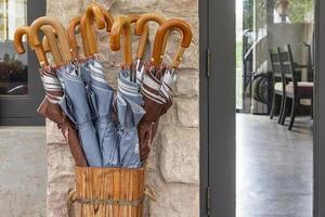 muitos guarda-chuvas dobrados armazenados em um recipiente de madeira em casa