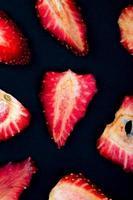 vista superior de fatias de morango isoladas em fundo preto foto
